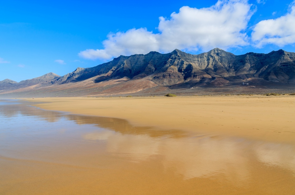 'Reflection of mountains in wet sand on Cofete beach in secluded part of Fuerteventura, Canary Islands, Spain' - Kanaren